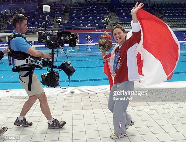 WAVE09/24/00 Canadian Olympic diver Anne Montminy parades her bronze medal in women's 10M platform diving for fans along poolside after the podium...