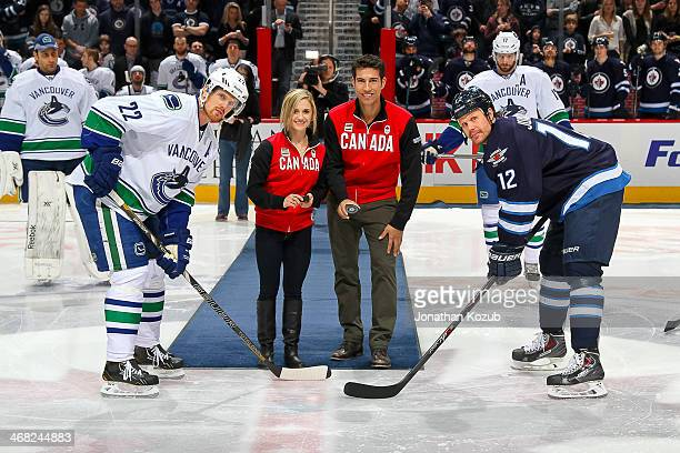 Canadian Olympic figure skaters Paige Lawrence and Rudi Swiegers get set to drop the ceremonial faceoff between Daniel Sedin of the Vancouver Canucks...