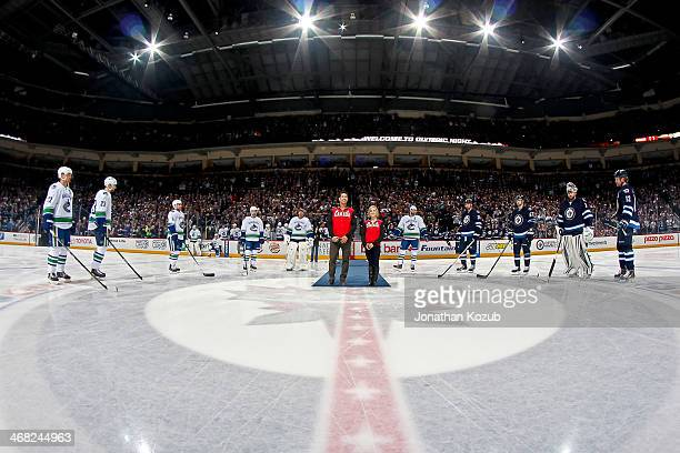 Canadian Olympic figure skaters Rudi Swiegers and Paige Lawrence stand at centre ice as they are honored alongside fellow Olympians from the Winnipeg...