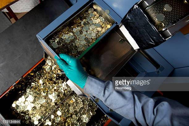 Canadian one dollar coins also known as Loonies fall into a container at the Royal Canadian Mint in Winnipeg Ontario Canada on Friday July 5 2013 The...