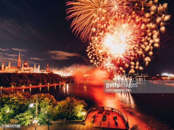 canadian parliament on ottawa river with fireworks - canadian flag stock pictures, royalty-free photos & images