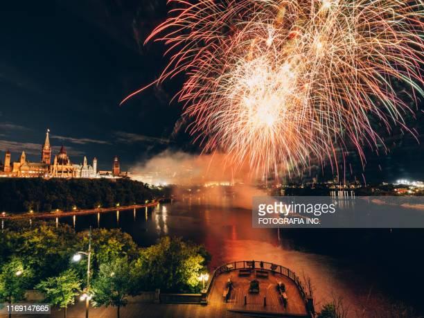 kanadisches parlament am ottawa river mit feuerwerk - ottawa stock-fotos und bilder