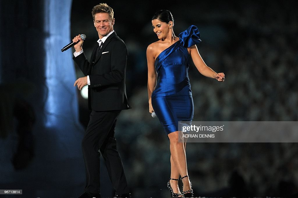 Canadian performers Bryan Adams (L) and Nelly Furtado sing during the opening ceremony for the Vancouver Winter Olympics at BC place in Vancouver on February 12, 2010. The Games' build-up culminates with the lighting of the Olympic cauldron at BC Place in Vancouver, a ceremony held indoors for the first time in the competition's history.