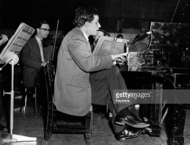 Canadian pianist-composer Glenn Gould rehearsing with an orchestra at the Royal Festival Hall, London for a series of Beethoven concertos, using a...