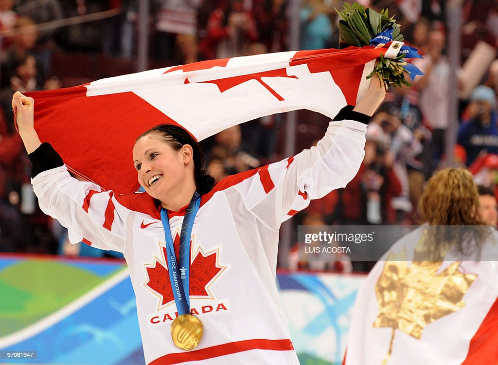 Canadian player skates with the national flag during the medals ceremony in the Woman's Ice Hockey games at the Canada Hockey Place during the XXI Winter Olympic Games in Vancouver, Canada on February 25, 2010. Canada beat the USA 2-0 to win the gold and Finland beat Sweden 3-2 to win the bronze.