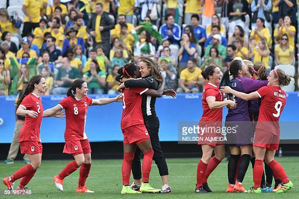Canadian players celebrate after their team's victory in their women's bronze medal football match between Brazil vs Canada at the Arena Corinthians...