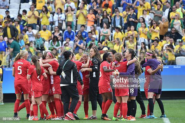 Canadian players celebrate after their team's victory in their women's bronze medal football match Brazil vs Canada at the Arena Corinthians Stadium...