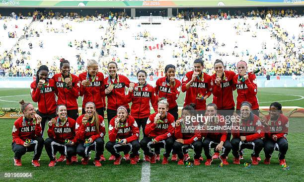 Canadian players pose for a photo after their team's victory in their women's bronze medal football match Brazil vs Canada at the Arena Corinthians...
