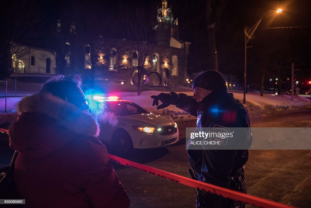 A Canadian police officer talks to a woman after a shooting in a mosque at the Québec City Islamic cultural center on Sainte-Foy Street in Quebec city on January 29, 2017. Two arrests have been made after five people were reportedly shot dead in an attack on a mosque in Québec City, Canada. / AFP / Alice Chiche
