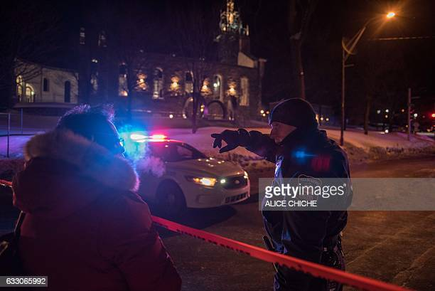 A Canadian police officer talks to a woman after a shooting in a mosque at the Québec City Islamic cultural center on SainteFoy Street in Quebec city...