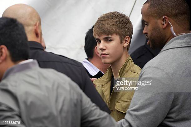 Canadian pop singer Justin Bieber is escorted by bodyguards after a photo opportunity before his concert as part of his 'My World Tour' at the Foro...