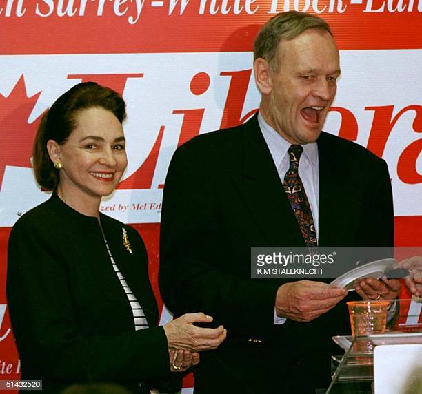 Canadian Prime Minister Jean Chretien, flanked by his wife Aline, receives a small gift following a rally in White Rock, British Columbia, 27 May....