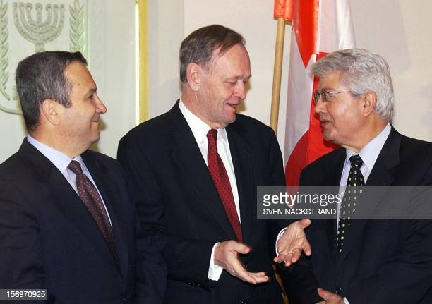 Canadian Prime Minister Jean Chretien talks to Israeli Foreign Minister David Levy as Israeli Prime Minister Ehud Barak looks on during their meeting...