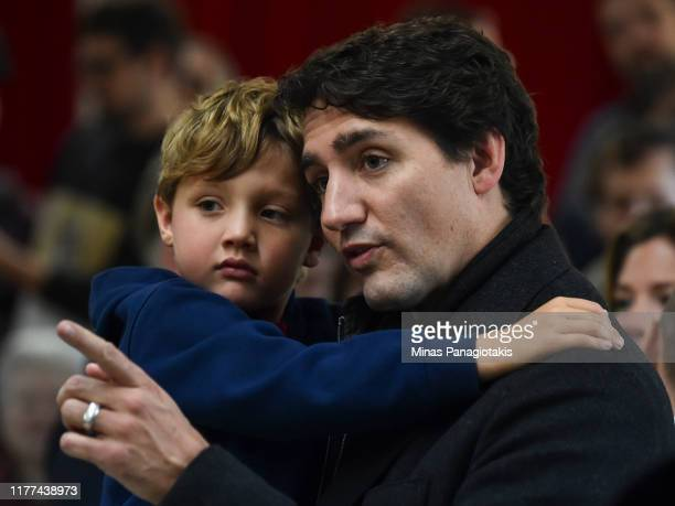 Canadian Prime Minister Justin Trudeau, accompanied by his youngest son Hadrien Trudeau, waits in line to cast his vote on election day at a polling...