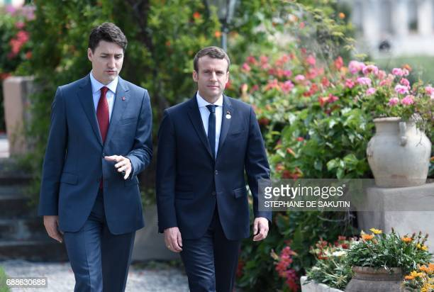 Canadian Prime Minister Justin Trudeau and French President Emmanuel Macron talk as they attend the Summit of the Heads of State and of Government of...