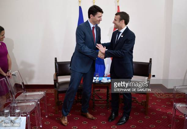 Canadian Prime Minister Justin Trudeau and French President Emmanuel Macron shake hands during a bilateral meeting as they attend the Summit of the...