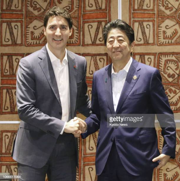Canadian Prime Minister Justin Trudeau and his Japanese counterpart Shinzo Abe shake hands in Port Moresby, Papua New Guinea, on Nov. 18, 2018....
