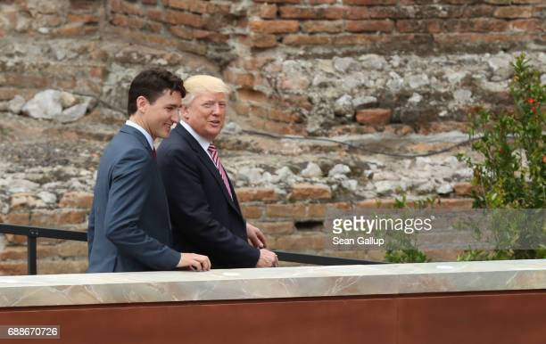 Canadian Prime Minister Justin Trudeau and US President Donald Trump depart after posing for the group photo at the G7 Taormina summit in the ancient...