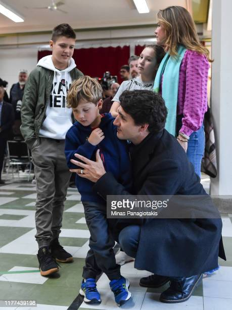 Canadian Prime Minister Justin Trudeau arrives to cast his vote as he holds his youngest son Hadrien Trudeau accompanied by older son Xavier Trudeau...