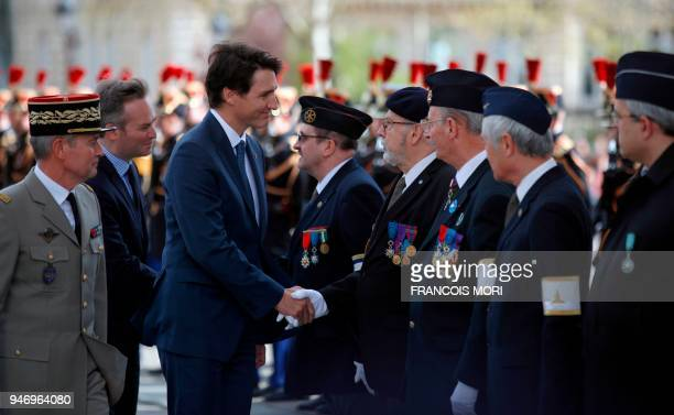 Canadian Prime Minister Justin Trudeau greets war veterans after a wreath laying ceremony on the Tomb of the Unknown Soldier at the Arc de Triomphe...