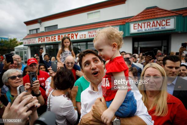 Canadian Prime Minister Justin Trudeau holds a baby as he greets supporters alongside local Liberal candidate Andrea Kaiser as he departs a campaign...