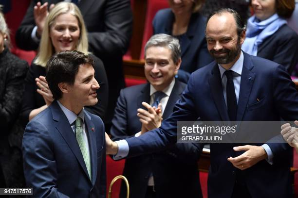 Canadian Prime Minister Justin Trudeau is applauded and greeted by French Prime Minister Edouard Philippe during a visit to the French National...