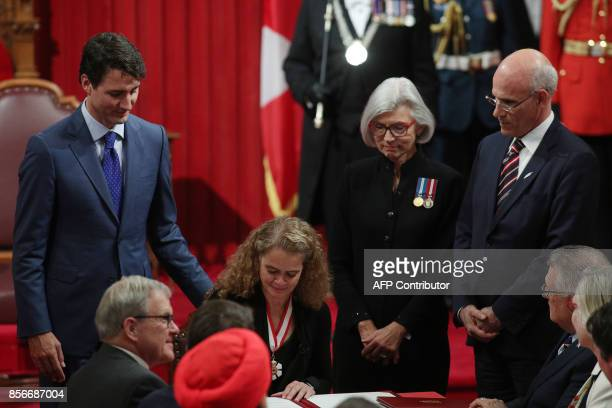 Canadian Prime Minister Justin trudeau looks on while Julie Payette signs the oaths in the Oath Book at the senate in Ottawa, Ontario, October 2,...