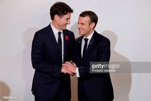 TOPSHOT Canadian Prime Minister Justin Trudeau shakes hands with French President Emmanuel Macron during the Paris Peace Forum at the Villette...