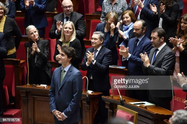Canadian Prime Minister Justin Trudeau smiles as he is applauded by members of the French Government and lawmakers during a visit at the French...