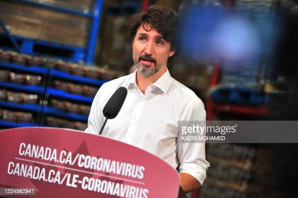 Canadian Prime Minister Justin Trudeau speaks to the press as he volunteers at the Moisson Outaouais food bank in Gatineau Quebec Canada on July 3...