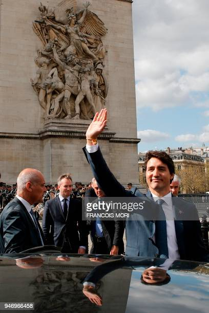 Canadian Prime Minister Justin Trudeau waves to onlookers as he enters his car after a wreath laying ceremony on the Tomb of the Unknown Soldier at...