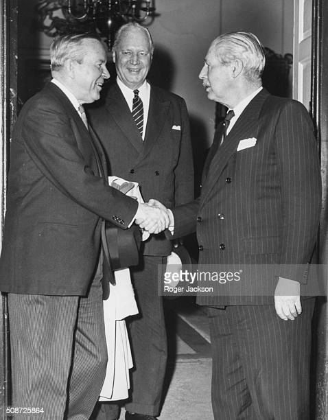 Canadian Prime Minister Lester B Pearson shaking hands with his British counterpart Harold Macmillan as George Drew the High Commissioner for Canada...
