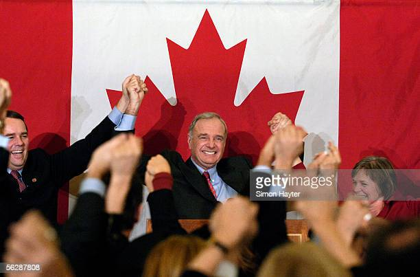 Canadian Prime Minister Paul Martin holds his arms up in a celebration at a Liberal Party caucus meeting following a vote vote of no confidence in...