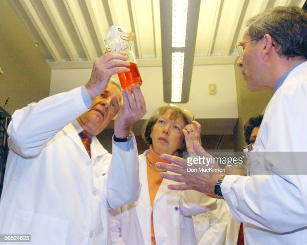 Canadian Prime Minister Paul Martin holds tumor cells in a tissue culture as his wife Sheila Martin and others listen to Dr Ralph Durand a...