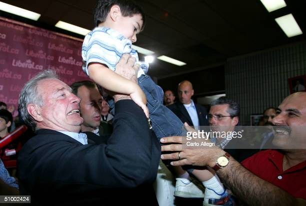 Canadian Prime Minister Paul Martin picks up a baby during a rally at the airport June 27, 2004 in Gatineau, Canada. Martin's Liberals and Stephen...