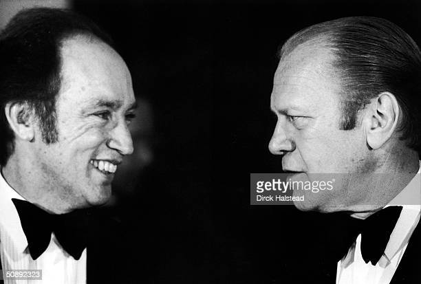 Canadian Prime Minister Pierre Trudeau laughs with American President Gerald Ford during a state dinner, November 4, 1974.