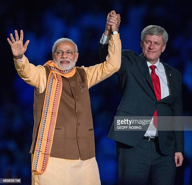 Canadian Prime Minister Stephen Harper and Indian Prime Minister Narendra Modi acknowledge the crowd during a rally on Prime Minister Modi's first...