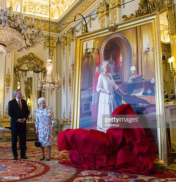 Canadian Prime Minister Stephen Harper stands with Queen Elizabeth II as she unveils a portrait of herself in the White Drawing Room at Buckingham...