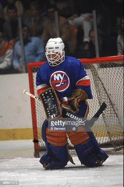 Canadian pro hockey player Billy Smith goalie for the New York Islanders guards the net during a road game 1980s