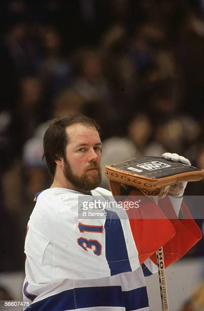 Canadian pro hockey player Billy Smith goalie for the New York Islanders stands with his helmet and face mask off holding his padding during a home...