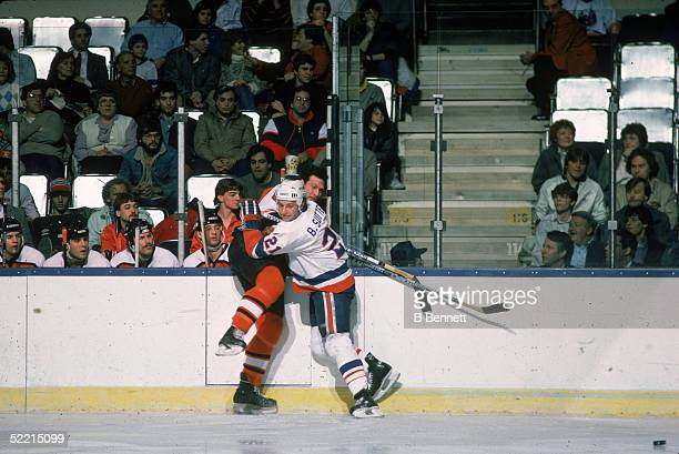 Canadian pro hockey player Brent Sutter forward for the New York Islanders hits Philadelphia Flyers defenseman Brad Marsh along the boards at Nassau...