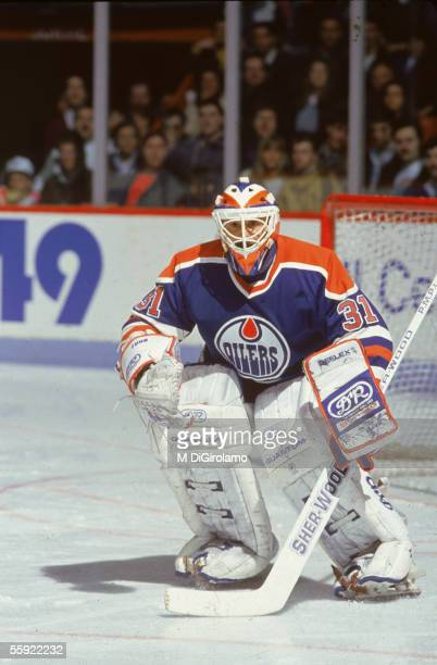 Canadian pro hockey player Grant Fuhr goalie for the Edmonton Oilers protects the net during an away game 1980s