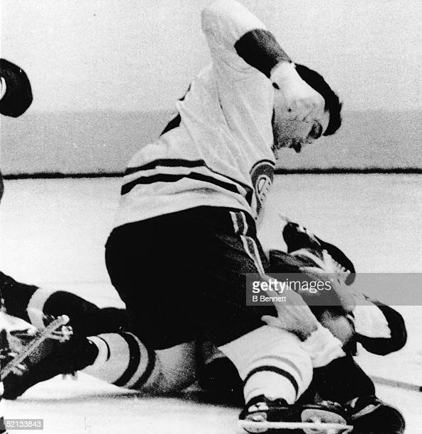 Canadian pro hockey player John Ferguson of the Montreal Canadiens punches an unidentified Kings player on the ice in the midst of a freeforall brawl...