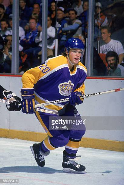 Canadian pro hockey player Luc Robitaille of the Los Angeles Kings tries to fight off an opponent during away game action 1980s