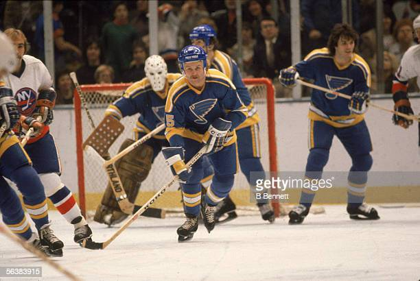 Canadian pro hockey player Tony Currie of the St Louis Blues moves the puck away from his team's goal during a game against the New York Islanders at...