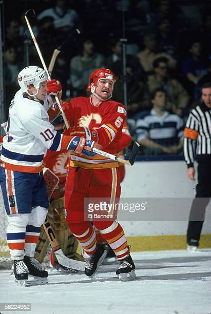 Canadian pro hockey players Alan Kerr of the New York Islanders and Neil Sheehy of the Calgary Flames lock sticks during a scuffle in a game at...