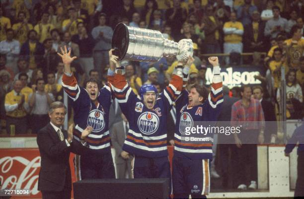 Canadian profesisonal ice hockey player Mark Messier of the Edmonton Oilers hoists the Stanley Cup over his head and shouts as he and teammates Kevin...