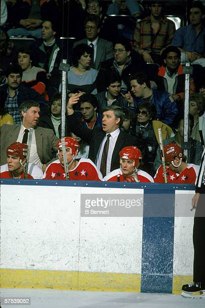Canadian professional hockey coach Bryan Murray head coach of the Washington Capitals gestures to his players on the ice from behind the bench during...