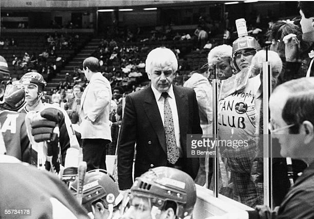 Canadian professional hockey coach of the Toronto Maple Leafs John Brophy walks past a fan who wears a shirt which claims the owner is a member of...