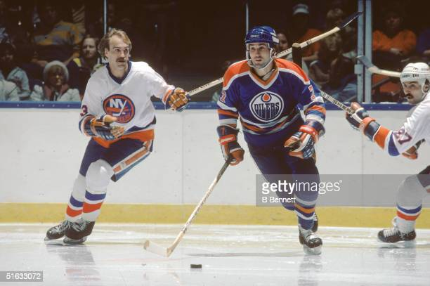 Canadian professional hockey player and 2004 Hall of Fame inductee defenseman Paul Coffey of the Edmonton Oilers skates against Bobby Nystrom and...